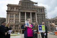 Ann Elder of Friendswood shows a photograph of her child, who was born a girl and who now identifies as her son, Benjamin, at a news conference outside the Texas Capitol in May.(File Photo/The Associated Press)