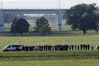 Officers saluted as a body presumed to be that of missing SMU police Officer Mark McCullers was carried from the Trinity River late Wednesday afternoon.<br>(Nathan Hunsinger/Staff Photographer)