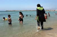 Nissrine Samali, 20, gets into the sea wearing a burkini, a wetsuit-like garment that also covers the head, in Marseille, southern France. France's top administrative court has overturned a town burkini ban amid shock and anger worldwide after some Muslim women were ordered to remove body-concealing garments on French Riviera beaches. (The Associated Press)