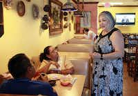 Elizabeth Villafranca, co-owner of Cuquitas Mexican restaurant in Farmers Branch, meets with customers Alejandra Osorio, left, and her husband Roman Osorio, on July 12, 2016.(Ben Torres/Special Contributor)