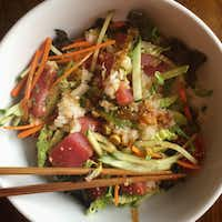 """Hoedupbap — Korean raw fish salad bowl — prepared from a recipe in """"Cook Korean!: A Comic Book with Recipes."""" After you assemble the dish, with freshly cooked rice on the bottom, then salad, then raw fish and garnishes on top, each person adds spicy dressing to taste and mixes it all up. (Leslie Brenner/Staff)"""