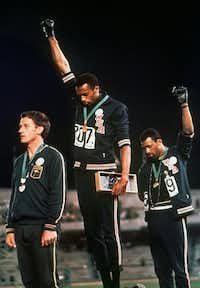 U.S. athletes Tommie Smith (center) and John Carlos (right) raised their gloved hands in protest at the 1968 Mexico City Olympics.(File Photo/The Associated Press)