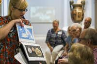 Emily Wiskera, manager of access programs, shows photos of Olympic medals during a presentation about ancient Greece as part of the Dallas Museum of Art's Meaningful Moments Program for individuals with early stages of dementia. (Ashley Landis/Staff Photographer)
