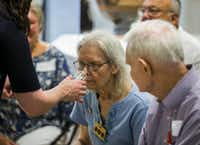 Sue Rath smells a sample scent of olive leaves as part of the Dallas Museum of Art's Meaningful Moments Program for individuals with early stages of dementia. (Ashley Landis/Staff Photographer)