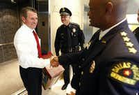 On his way out of police headquarters for the last time in 2010, outgoing Dallas Police Chief David Kunkle (left) ran into newly sworn-in Police Chief David Brown. (Tom Fox/Staff Photographer)