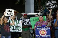 People hold up signs of protest during the protest against Dakota Access Pipeline at Chief Oil & Gas Headquarters on Sept. 2, 2016 in Dallas. (Ting Shen/The Dallas Morning News)(Ting Shen/Staff Photographer)