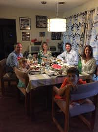 Attorney General Ken Paxton, far left, and his wife, Angela, far back, eat dinner on Thursday with the Briggles: parents, Adam and Amber; 8-year-old son MG; and 4-year-old daughter Lulu.(Photo courtesy of Equality Texas)