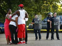 Lashaun Bradford (far left) joined others including her son Raymon Bradford (in red hat) at a police line in Dixon Circle to pray over the loss of James Harper in July 2012. Hundreds of people converged near where Harper was shot while running from police in southeast Dallas. Police in riot gear had to control an angry crowd that formed after the officer-involved shooting.(Tom Fox/Staff Photographer)