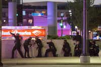 Dallas police take up positions along a wall at the corner of Lamar and Main streets as they train their weapons toward the El Centro College campus minutes after shots were fired at the conclusion of a Black Lives Matter rally downtown on July 7. (Smiley N. Pool/Staff Photographer)