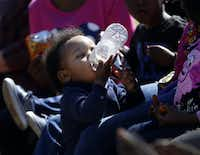 One-year-old John Miller drinks bottled water during a prayer vigil outside Mt. Zion Baptist Church in the unincorporated community of Sandbranch in February.(Rose Baca/ Staff Photographer)