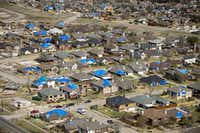 Blue tarps dot rooftops of tornado damage neighborhoods in Rowlett in February.(G.J. McCarthy/Staff Photographer)