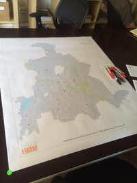 A large map of Dallas stretches across a table in buildingcommunityWORKSHOP. Community members gathered to place stickers on areas around the city where they thought a Little Free Library would be best placed.(Kaitlynn Martin / Staff<br>)