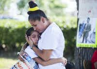 Jose Cruz's mother, Ana Henriquez, comforts Cruz's sister, Stephanie Eschriche, near Cruz's burial site on Sept. 9, 2016, at Crown Hill Memorial Park in Dallas. (Ashley Landis/Staff Photographer)