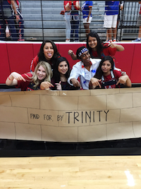 """Students with a pep rally sign that depicts the """"wall"""" Donald Trump wants to build along the Mexican border, with a message that says """"paid for, by Trinity."""" A student who posted the photo says school administrators approved the signs. (Twitter)"""