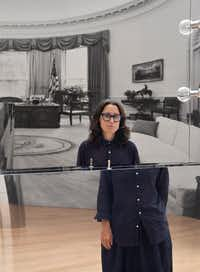 "Artist Kathryn Andrews is photographed at the ""Run for President"" exhibition in a reflection of <i>Die Another Day</i>, 2013, polished stainless steel, glass, brass and certified prop with Oval Office during the Reagan Administration, The White House, 1981-89, reflected in the background. (Nan Coulter/Special Contributor)"