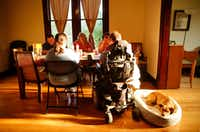 The Rev. Justin Hancock (right) and his wife, Lisa, join visitor Matt Harrell (facing, left) and residents Macie Liptoi and Rebecca Mitts for morning prayer over breakfast at the Cochran House in Dallas. The Hancocks founded the Julian Way, a project aimed at bringing disabled and able-bodied women and men of faith together to live in a community house, similar to the one they live in now. (Tom Fox/Staff Photographer)