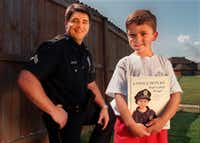 ORG XMIT: S11A47F11 Dallas police Senior Cpl. Ronald Pinkston with his son Trevor Pinkston, 6, who holds a book his father wrote for him.  Cpl. Pinkston,37, wrote the book about a child who wishes to become a police officer and published it using a significant amount of his own money.  They are in the backyard of their Rowlett home. Trevor's likeness is on the cover of the book. 06202013xNEWS(Natalie Caudill/130408)
