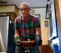 Alfonso Cevola takes a completed Eggplant Parmigiana out of the oven.(Nathan Hunsinger/Staff Photographer)
