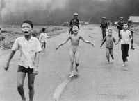 In this June 8, 1972, photo taken by Nick Ut, 9-year-old Kim Phuc (center) runs with her brothers and cousins, followed by South Vietnamese forces, down Route 1 near Trang Bang after a South Vietnamese plane accidentally dropped its flaming napalm on its own troops and civilians. The terrified girl had ripped off her burning clothes while fleeing.(Nick Ut/The Associated Press )