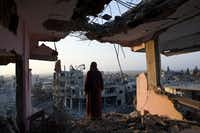 Palestinian woman Hidya Atash overlooks the destruction in Shujayea neighborhood of Gaza City at dawn Aug. 8, 2014. On Friday the 72 hour cease fire came to an end without a longer term agreement. Rockets fired by Palestinian militants hit Israel and Israel resumed its air strikes.(Heidi Levine/Sipa Press)