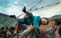 In this photo, part of Carol Guzy's Pulitzer Prize-winning portfolio, Kosovar refugee Agim Shala, 2 years old, is passed through the barbed wire fence into the hands of grandparents at the camp run by United Arab Emirates in Kukes, Albania. The members of the large Shala family were reunited here after fleeing Prizren in Kosovo during the conflict. . (The grandparents had just crossed the border at Morina). The relatives who just arrived had to stay outside the camp until shelter was available. The next day members of the family had tents inside. The fence was the scene of many reunions. When the peace agreement was signed, they returned to Prizren to find their homes only mildly damaged. There were tears of joy and sadness from the family as the children were passed through the fence, symbolic of the innocence and horror of the conflict. (Carol Guzy/The Washington Post)