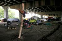 "Amid a makeshift cross, homeless residents live in an encampment beneath Interstate 30 near Fair Park.(<p>(Tony <span style=""font-size: 1em; background-color: transparent;"">Gutierrez/</span><span style=""font-size: 1em; background-color: transparent;"">Associated Press)</span></p>)"