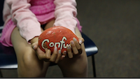 "A participant in the Five Star Kids program holds a stone painted with the word ""confused"" during a session at the Betty Ford Center.(Hazelden Betty Ford Foundation)"