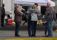 Burlington Mayor Steve Sexton hugs one of the victims' family members outside Cascade Mall.(Ruth Fremson/The New York Times)