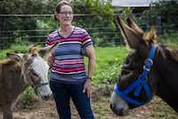 Elizabeth Hendel of Royce City, Texas stands between donkeys Ethel and Charlie.(Ashley Landis/Staff Photographer)