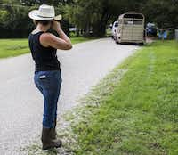 Jess Anselment wipes away a tear as Elizabeth Hendel of Royce City, Texas drives away with two adopted donkeys.(Ashley Landis/Staff Photographer)