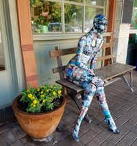 A decoupaged sculpture of a woman on a bench sits outside the office of the twice-weekly Williamson County Sun in Georgetown. (Helen Anders)