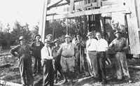 "H.L. Hunt, in white shirt with cigar in his mouth, in front of the Dasy Bradford No. 3, the oil well that marked the beginning of the massive East Texas oil field and his rise to huge riches. C.M. ""Dad"" Joiner, (third from left) shakes the hand of geologist Dr. A.D. Lloyd"