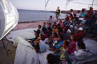 Refugee children watched a movie at an island camp in Greece this week. (Louisa Gouliamaki/Agence France-Presse)