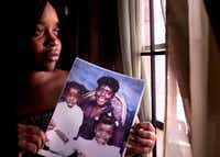 Shennel Gardner held a portrait of her brother, Devon Green (left); her mother, Debra Gardner (center); and herself in 2011. Shennel and Devon were present when their mother, Debra, was fatally shot by Duane Buck in 1995.(Cody Duty/Houston Chronicle)