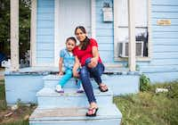 Joanna Pena and daughter Zaory Rendon, 4, sit on the stoop of their West Dallas home, which the owners, HMK, say they'll need to vacate no later than Oct. 31.((Ashley Landis/Staff Photographer))