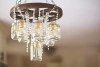 """A wagon wheel and mason jar chandelier is dripping with crystals in a Junk Gypsy-designed farmhouse kitchen.(<p><span style=""""font-size: 1em; background-color: transparent;"""">April Pizana Photography</span><br></p><p></p>)"""