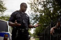 Dallas police Sr. Cpl. Melvin Williams talks with a woman in the Pleasant Grove area of Dallas. (G.J. McCarthy/Staff Photographer)
