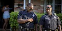 Dallas police Sr. Cpl. Melvin Williams (left) and Officer Paul Smith walk to their squad cars after speaking with a woman in response to a call on Aug. 21 in the Pleasant Grove neighborhood. (G.J. McCarthy/Staff Photographer)