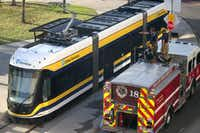 Dallas firefighters climbed on top of their truck to talk about a small electrical fire that was burning on top of a Dallas Streetcar at the terminus of the line that runs from downtown to Oak Cliff on Monday. (Guy Reynolds/Staff Photographer)