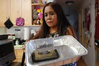 Dee Decasa holds her replacement Galaxy Note 7 smartphone in an aluminum pan at her home in Honolulu on Monday, Oct. 10, 2016, one day after the phone released smoke and sizzled. (AP Photo/Audrey McAvoy)AP