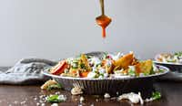 Putting buffalo sauce on Buffalo Chicken Nachos(Rebecca White)
