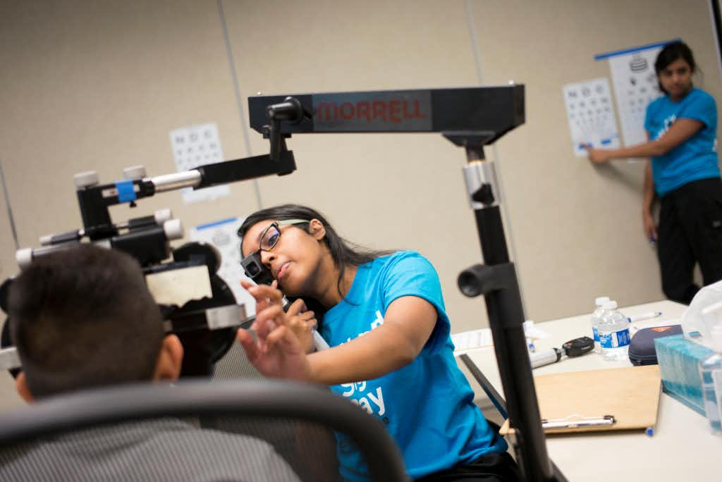 Volunteer Ashley Varghese (center) exams a Carrollton ISD student's eye during the free eye exams provided by Essilor Vision Foundation during World Sight Day  at Essilor of America on Oct. 13, 2016 in Dallas, Texas. Ting Shen/Staff Photographer