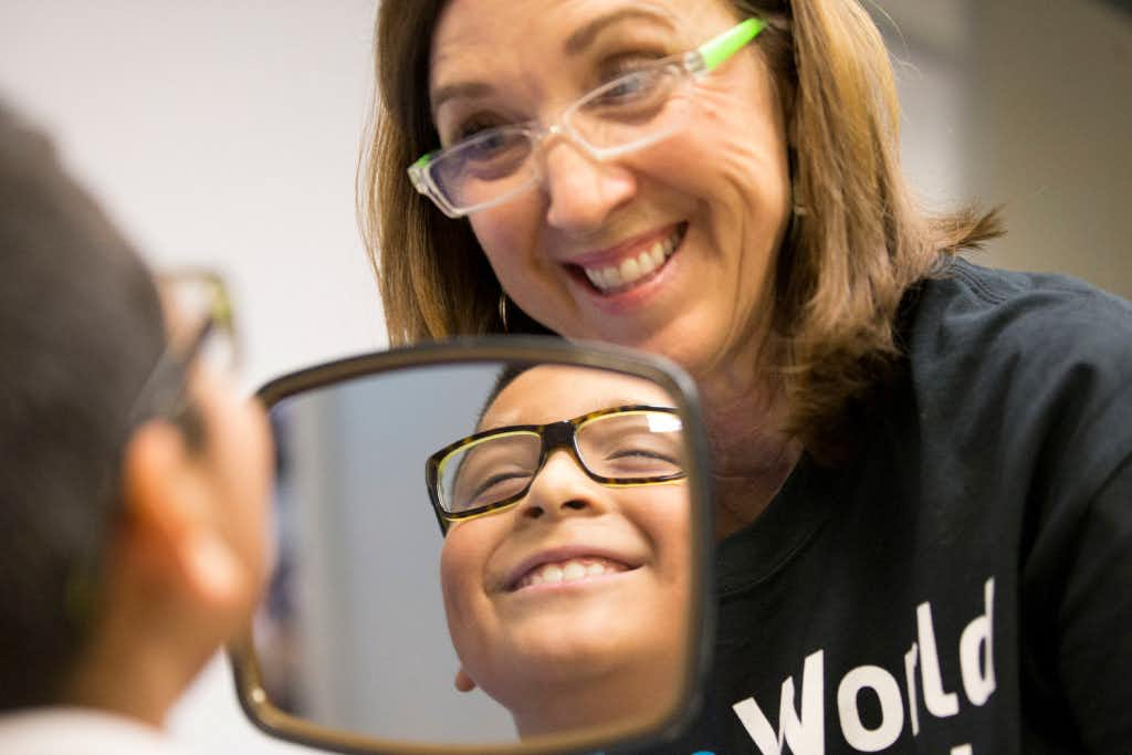 Diane Hirtriter of Kids Vision for Life, helps Damian Garcia, 8, of Carrollton, Texas pick out glass frames during free eye exams provided by Essilor Vision Foundation during World Sight Day at Essilor of America on Oct. 13, 2016 in Dallas, Texas.Ting Shen/Staff Photographer