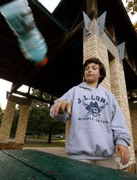 Ian Interrante, 12, demonstrates the flipping bottles game at Lindsley Park in Dallas.(Nathan Hunsinger/Staff Photographer)