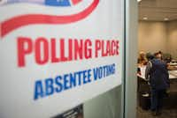 A woman registers to vote at an absentee voting station in Arlington, Va. (Andrew Caballero-Reynolds/Agence France-Presse)