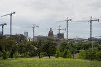 "The Texas State Capitol building stands beyond construction cranes at the University of Texas at Austin campus this month. Cities in the West and Southwest are experiencing economic growth exceeding records set before the financial crisis as young, educated workers migrate west to create housing shortages and drive up wages. Moved Monday, April 27, 2015. (<p><span style=""font-size: 1em; background-color: transparent;"">Bloomberg News photo by Matthew Busch</span></p>)"