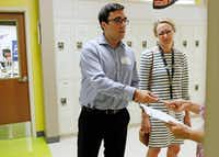 SMU law student Jake Torres helps a tenant at an emergency legal clinic set up on Wednesday at Uplift Heights preparatory school in West Dallas. Becky Madole of Uplift looks on. (Ben Torres/Special Contributor.)