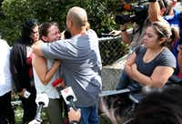 Relatives of Anthony Garcia, 24, who was killed Wednesday by a Dallas police officer, gathered nearby as they waited for information about the shooting. Some of them shouted expletives at officers but were quickly held back by others.(Rose Baca/Staff Photographer)