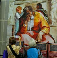 Visitors look at the photo reproduction of the Sistine Chapel at Fair Park. (Nathan Hunsinger/The Dallas Morning News)