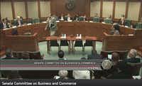 Ware V. Wendell, leader of Texas Watch, is shown at center walking away from Texas Senate Business and Commerce Committee Chairman Kelly Hancock (R-North Richland Hills) in October 2016. Any insurance bill in the 2017 session will pass through Hancock's committee.
